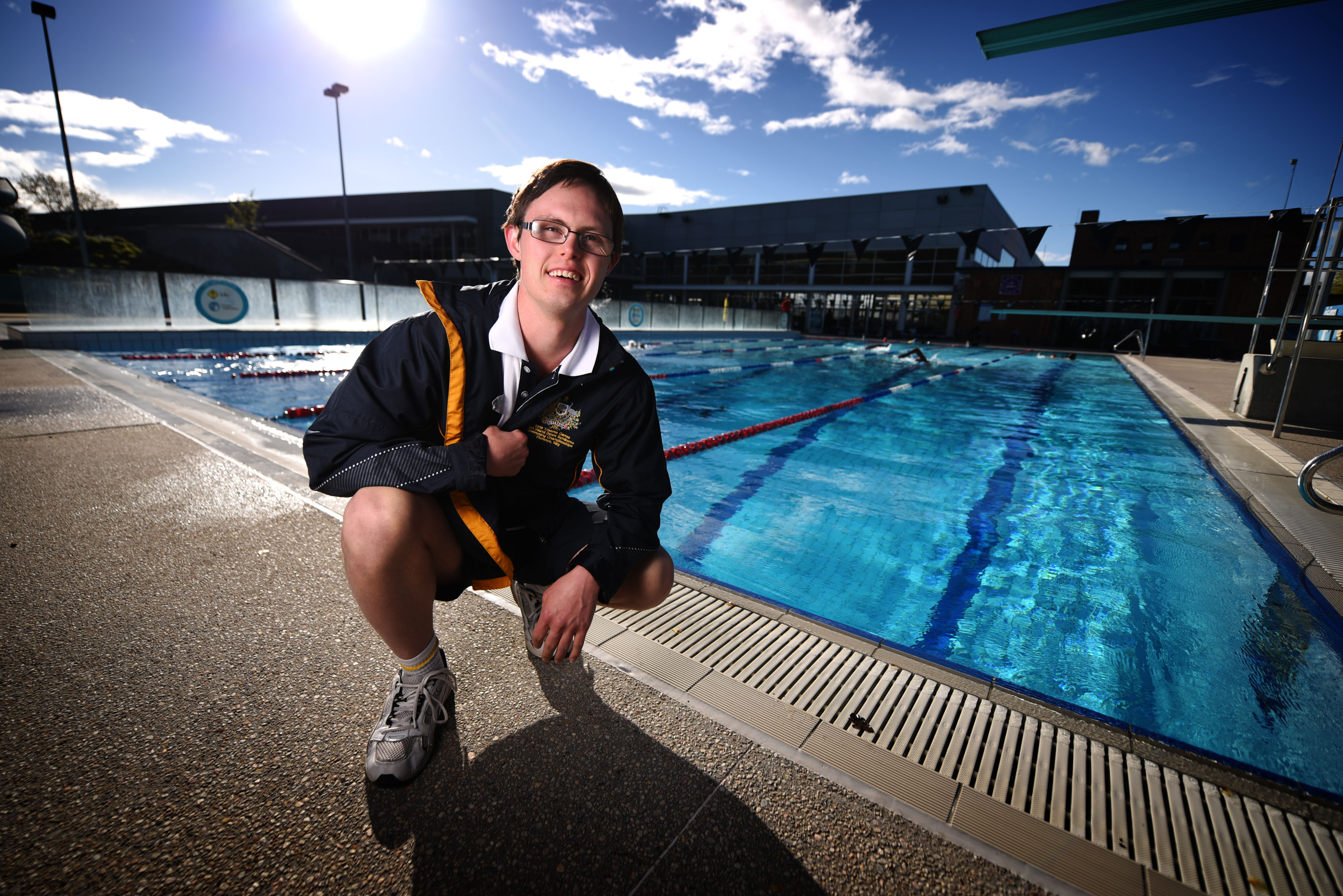 Young person kneeling by outdoor swimming pool on a sunny day