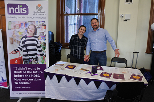 A man and a woman standing at an NDIS display.