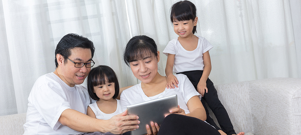 Stock image of happy family group seated on couch around a notebook computer screen