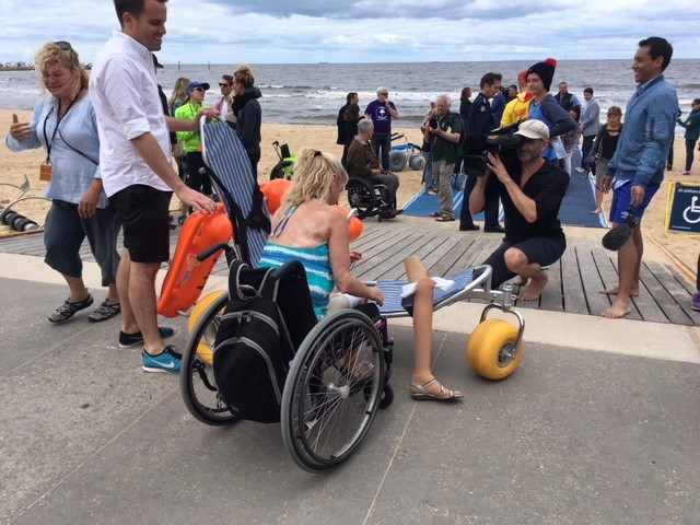 Image of a lady preparing to use her floating wheelchair
