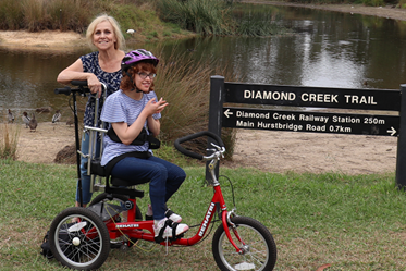A young woman on a bike, posing for a photo by the creek with her mother