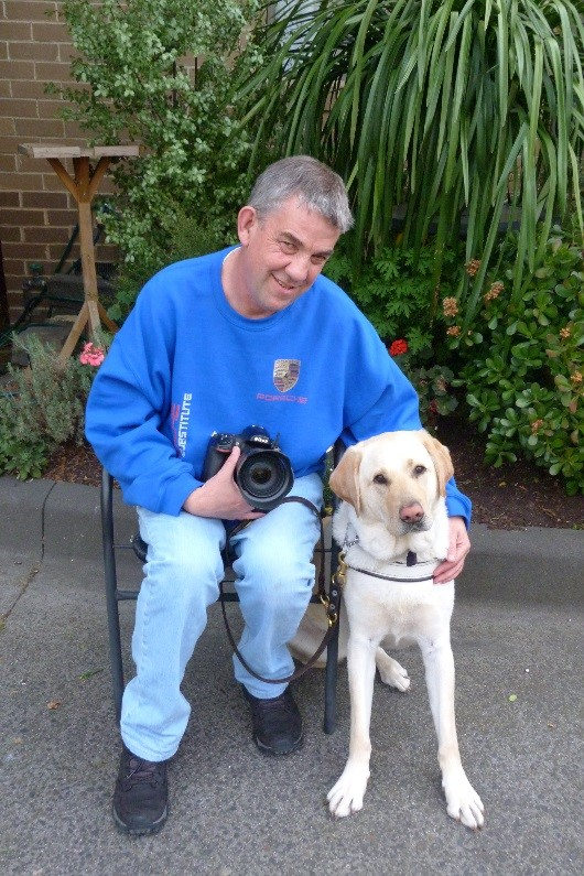 A man holding a camera and posing with his guide dog