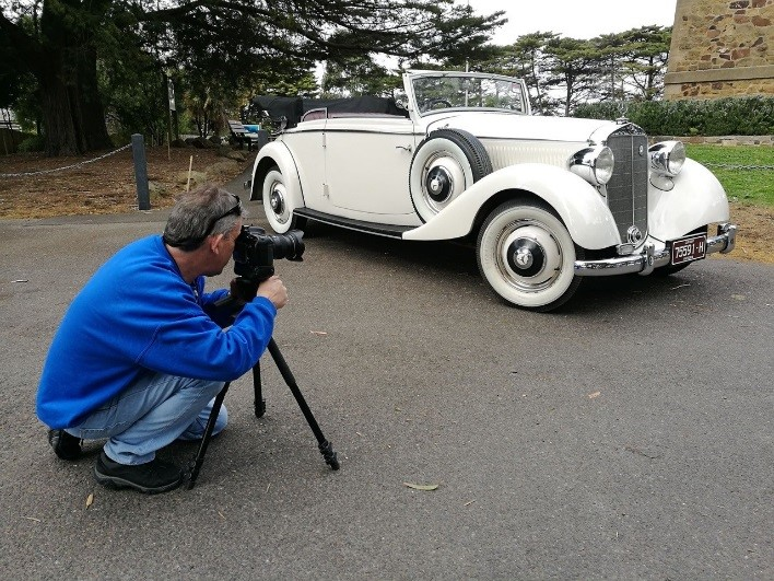 A man photographing an older style car