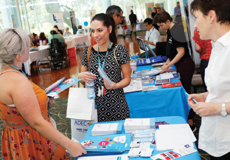 Three people in discussion at an expo stall