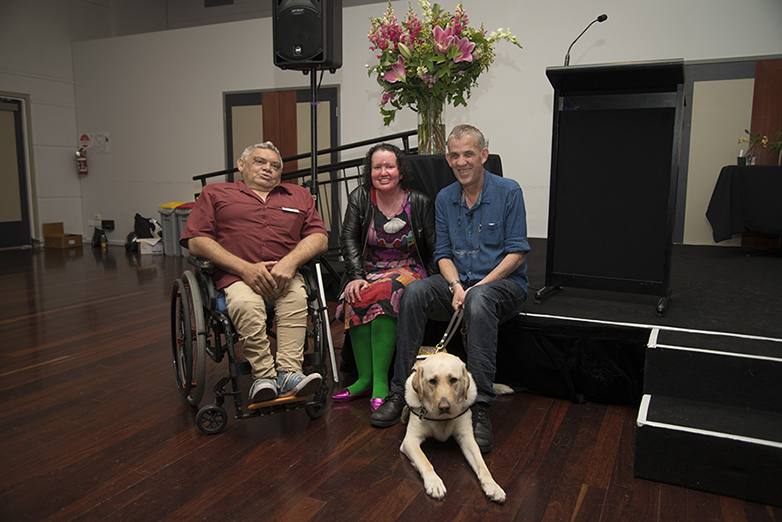 A woman, two men and a guide dog pose for a photo in front of a vase of pink flowers
