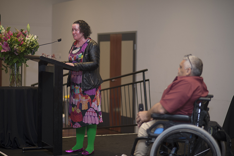 A woman in green tights giving a speech at a lectern while another woman looks on