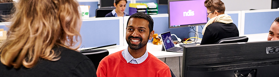 Man sitting at a desk smiling at a colleague.