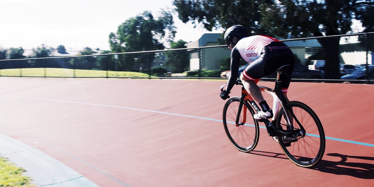 A cyclist leaning over their bike cycling at speed round an asphalt track