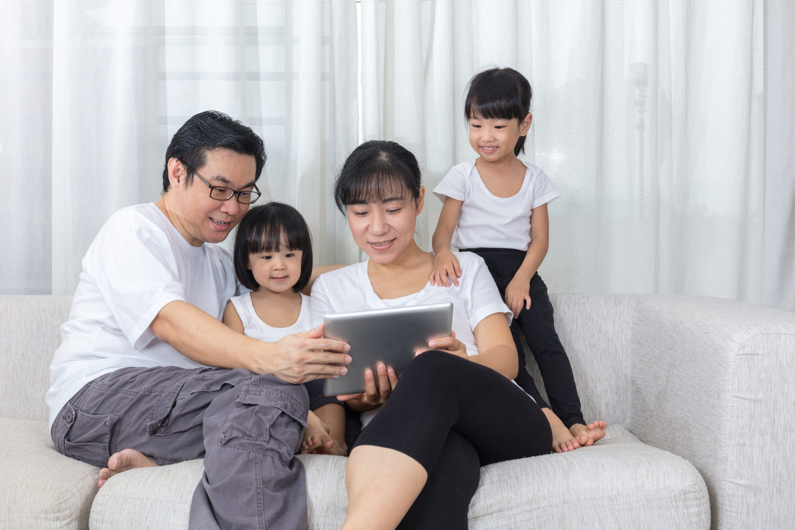 Happy Asian Chinese family using tablet on the couch in the living room at home.