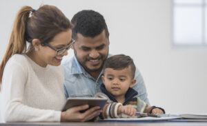 Mum, Dad and toddler looking on an iPad