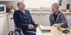 a man in a wheelchair laughing with a young man