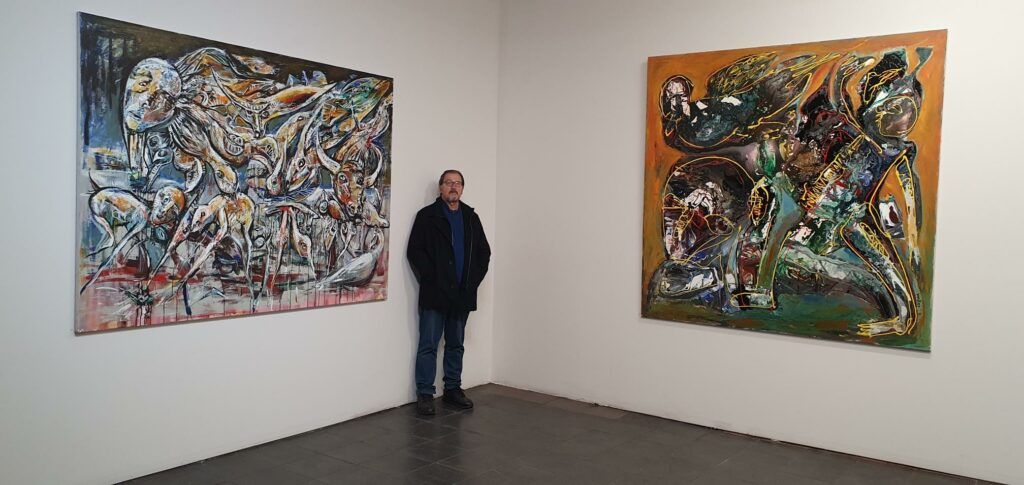 Milos stands between two of his paintings at his solo art exhibition.